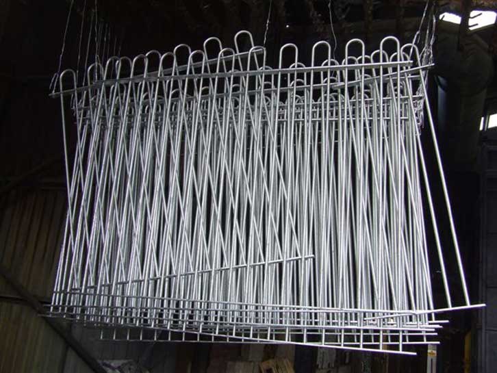 mild steel sections of bow top fencing after being removed from molten zinc bath as part of the hot dip galvanizing process to B.S. EN. ISO 1461 (2009)