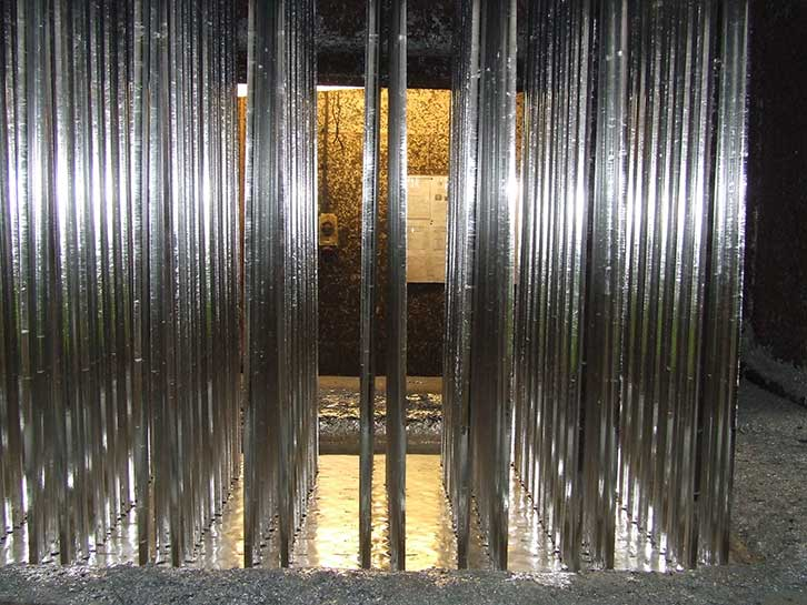 mild steel sections of Palisade fencing after being removed from molten zinc bath as part of the hot dip galvanizing process to B.S. EN. ISO 1461 (2009)