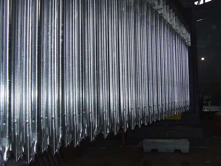 mild steel sections of Palisade fencing after being removed from molten zinc bath as part of the hot dip galvanizing process.