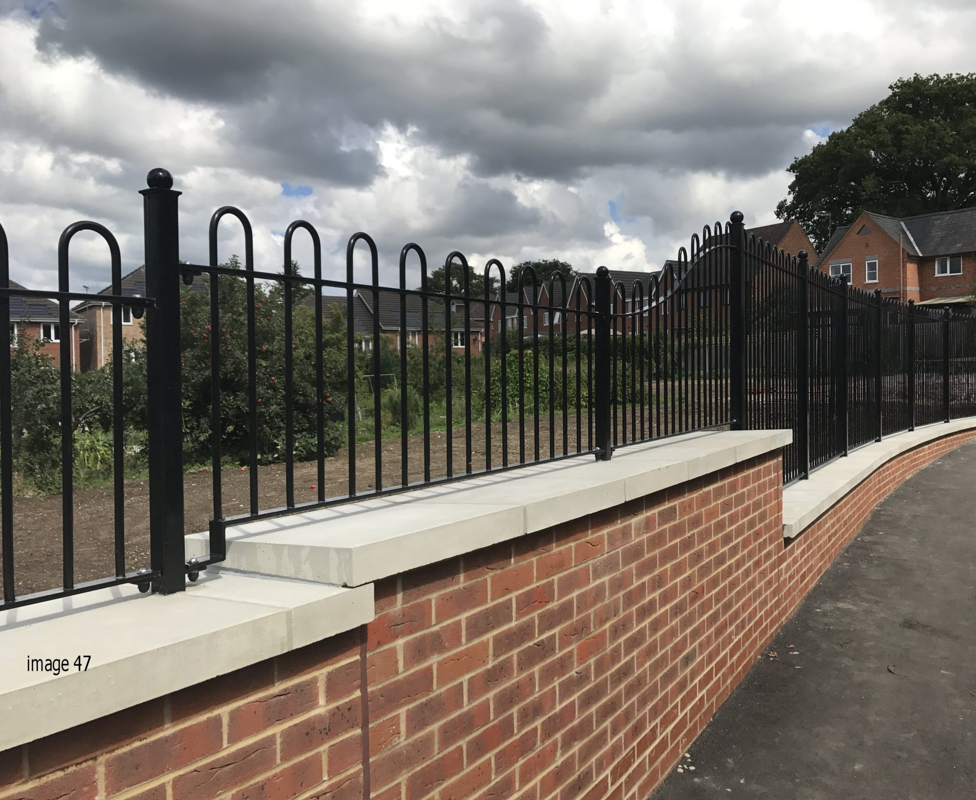 galvanized and powder coated bow top railings along top of wall