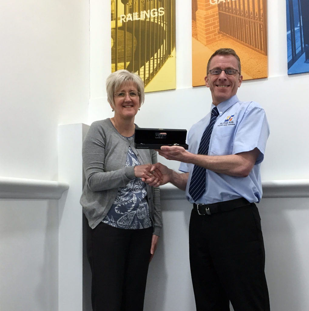 Finance Director Mark Sipson presents Yvonne with new bracelet to celebrate